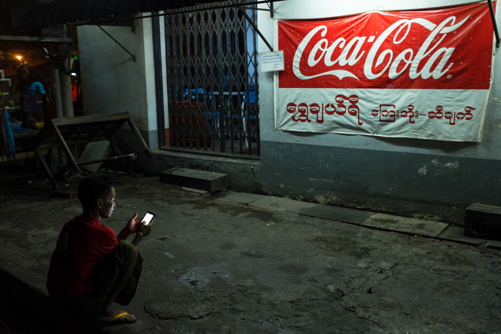 Closing time at a Yangon restaurant in the new cellphone era.