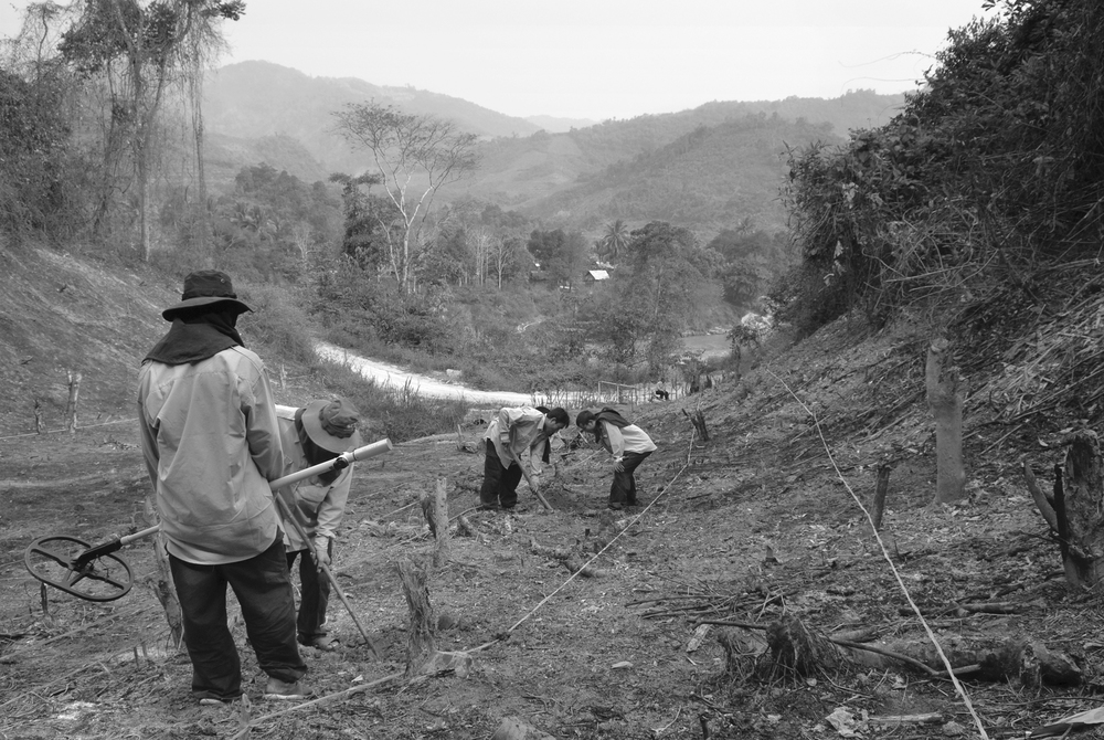A bomb clearance team from the Australian company Phoenix Clearance LTD carefully searches for UXO in a new garden plot in rural Phongsali Province, in Northern Laos. The plot belongs to the local doctor, and the clearance team eventually found live cluster munitions just inches under the surface.