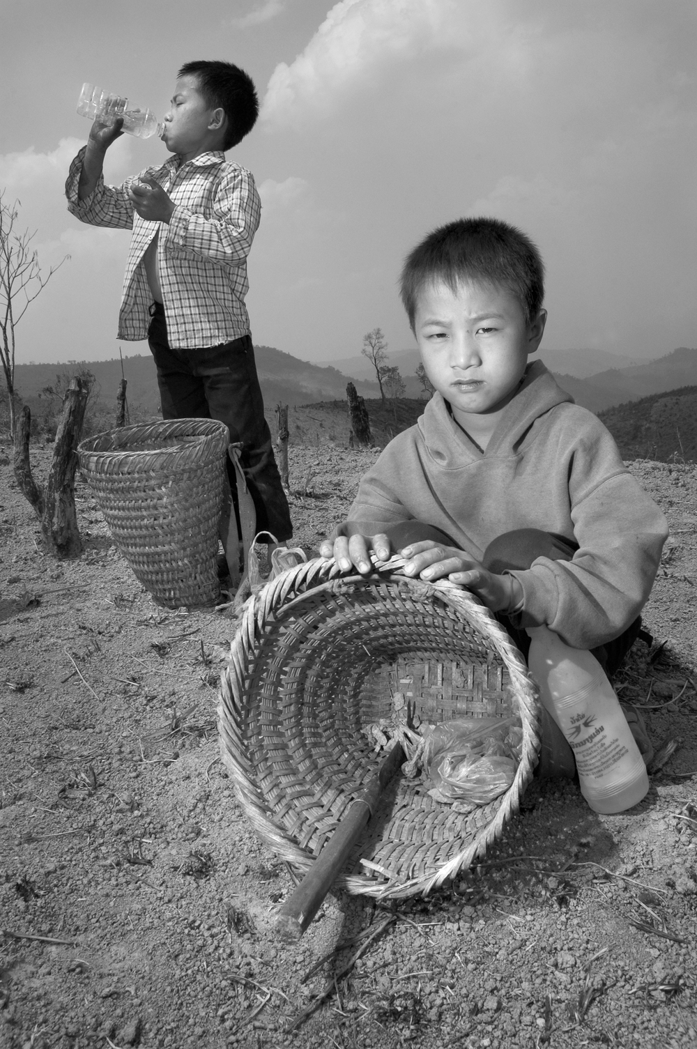 Teng, an 8-year-old Hmong boy, takes a break from scavenging bomb scraps with a friend, in the ashes of a burned field in the middle of Xieng Khouang province, Laos.