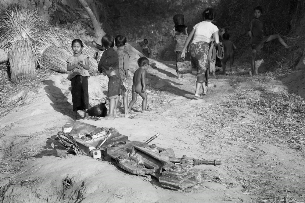 After gathering water and washing in a nearby river, families walk past the landing gear from a US airplane that was shot down over the Ho Chi Minh Trail in southern Laos. Villagers found the valuable piece of scrap metal in the nearby forest, but the several-hundred-pound chunk is too heavy to carry to market.