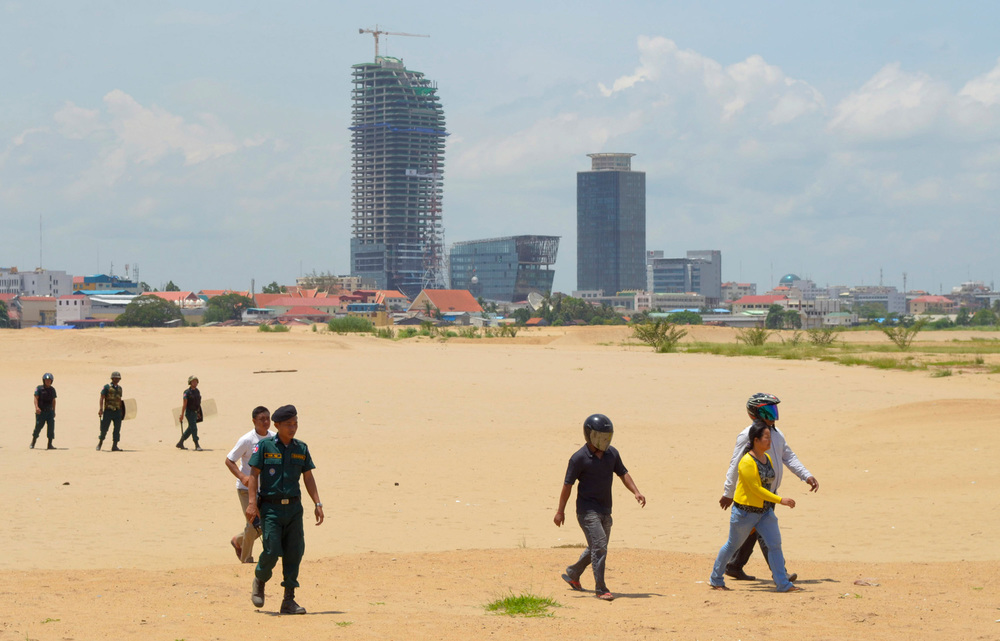 Plainclothes and uniformed police escort a protestor across the former Boeung Kak Lake following her arrest. She was one of twelve women arrested for protesting the loss of their homes to a commercial development by Shukaku Corporation, which has since filled in the lake with sand.