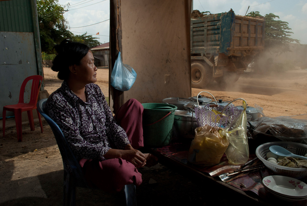 A woman watches construction trucks pass her small shop west of Phnom Penh. She and hundreds of her neighbors were evicted from their homes near the river in Phnom Penh and moved to a new satellite town outside the city.