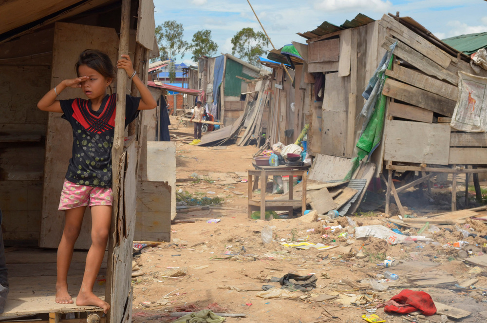 A girls wipes dust from her eyes as she stands in her family's shack in the worker's quarters at the Bali Resort Cambodia construction site in Phnom Penh.
