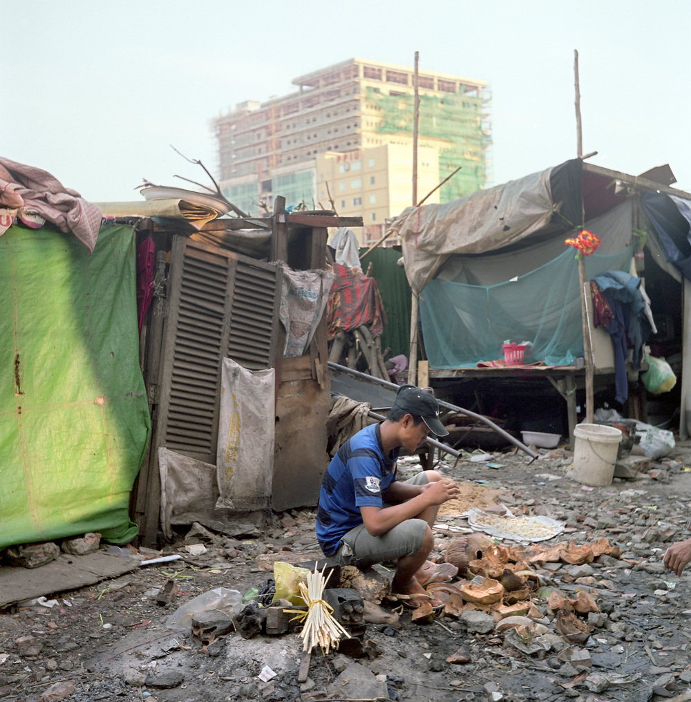 A young man sits next to a fire in the shanty village in the rubble of the Borei Keila community.