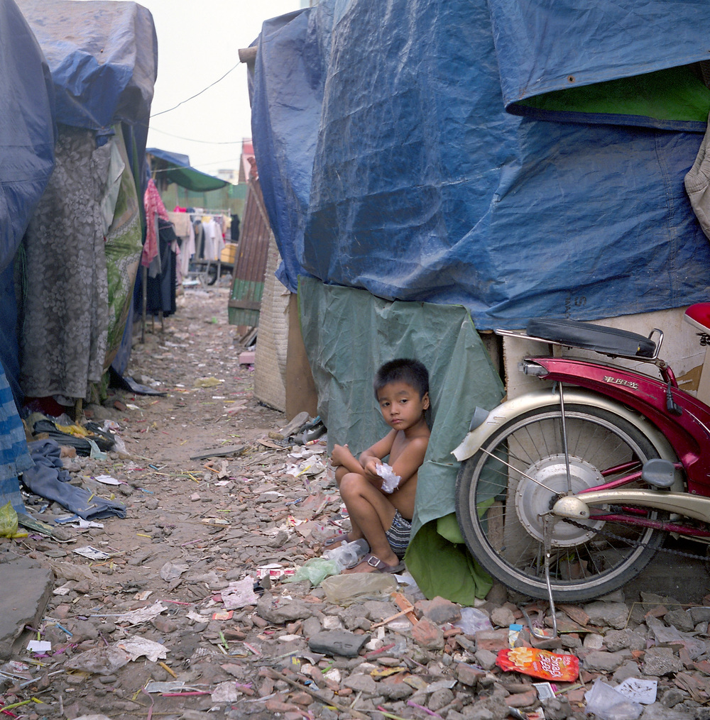 A boy squats outside his family's tarp shanty on the remains of the Borei Keila housing development. Dozens of homes were bulldozed to make room for new buildings, but many of the families were neither compensated nor given new homes.