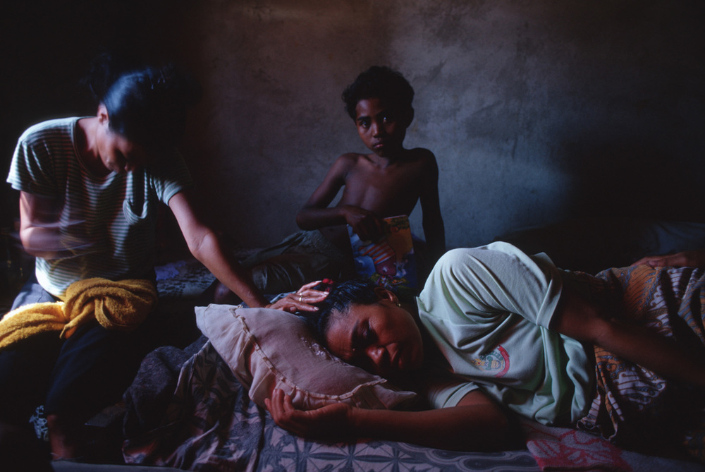 Romana Goncalves, 43, is comforted by two of her six children as she slowly dies of a uterine tumor at her home in Dili, Timor Leste. She did not have the $2,000 needed for an operation to help her.