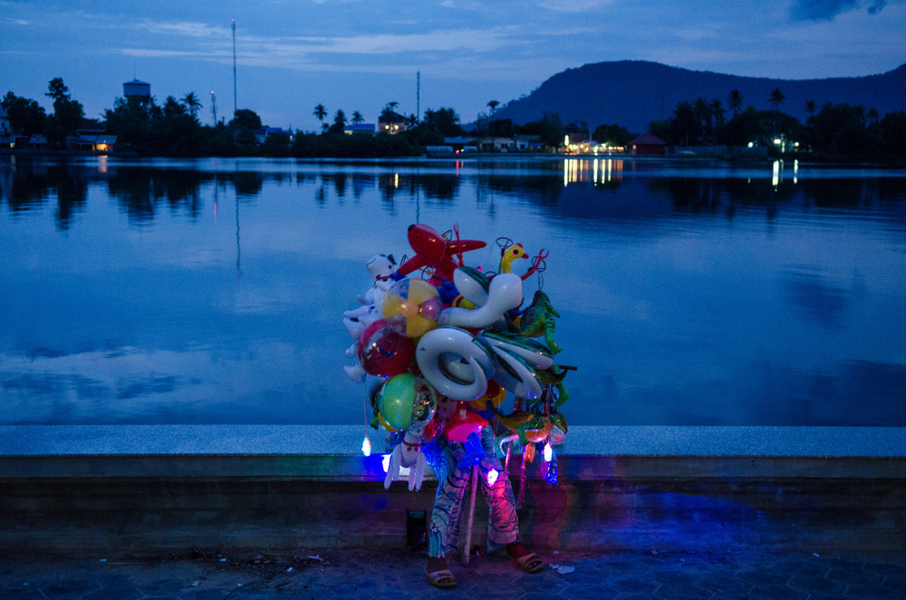 A woman sells toys and balloons along the riverfront in Kampot, Cambodia.