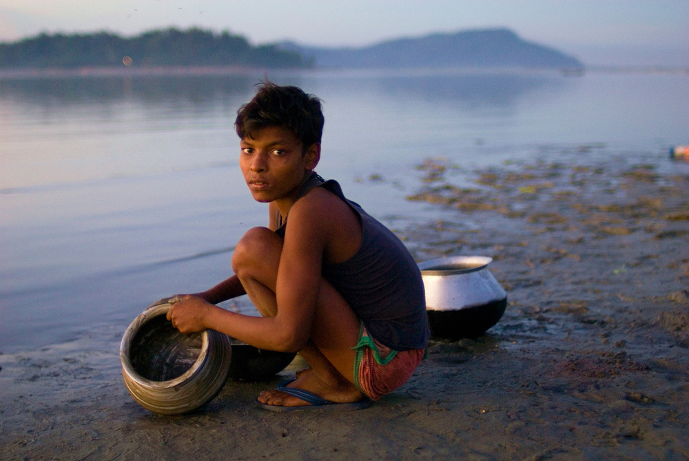 Washing dishes in the Brahmaputra River, Guwahati, India.