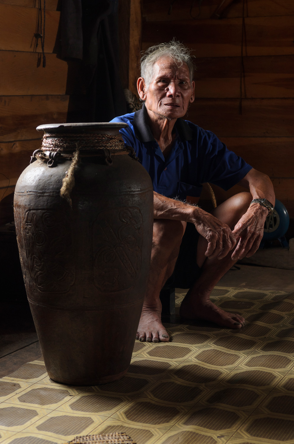 "Uun Paran sits next to a Chinese ""dragon jar"" in his home in Pa Lungan. For centuries, Kelabit people used jars like this to store rice wine and - with their tops lopped off and then reattached - as burial jars. They were also a symbol of a family's wealth and status."