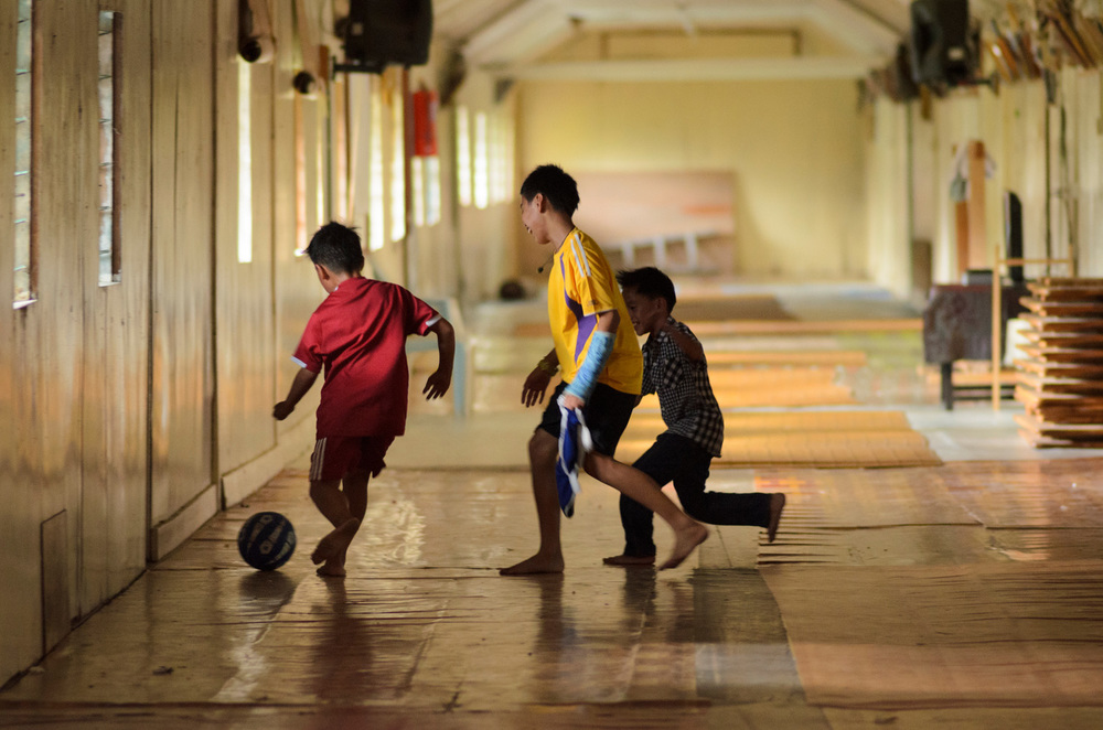 Boys play soccer in an empty great hallway of the Bario Asal longhouse in Bario. The hallway, with doors to individual family apartments, is more and 100 meters long.