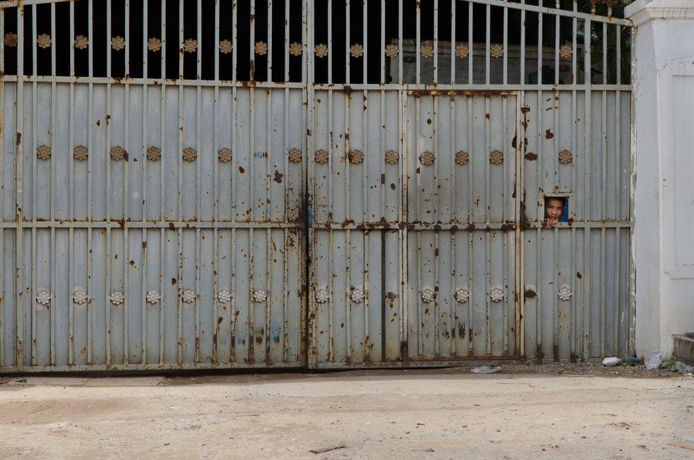 A guard keeps an eye on people passing in front of a garment factory gate in Phnom Penh. Cambodian garment factories are usually very secretive and generally restrict access to their facilities as a matter of course to anyone not working there.
