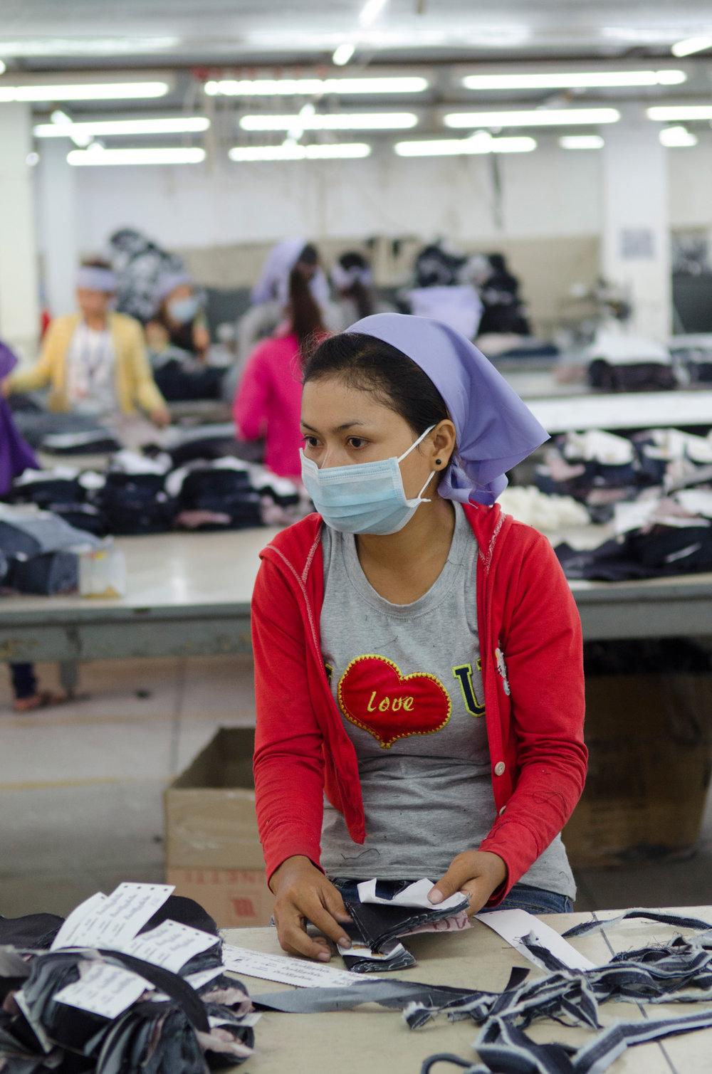 A worker at the Meng Ieng Group (MIG) Garment Factory sorts and bundles pocket patches for denim jeans on the main factory floor in Phnom Penh. Many in Phnom Penh's factories wear face masks to filter out the dust created from cutting cloth.