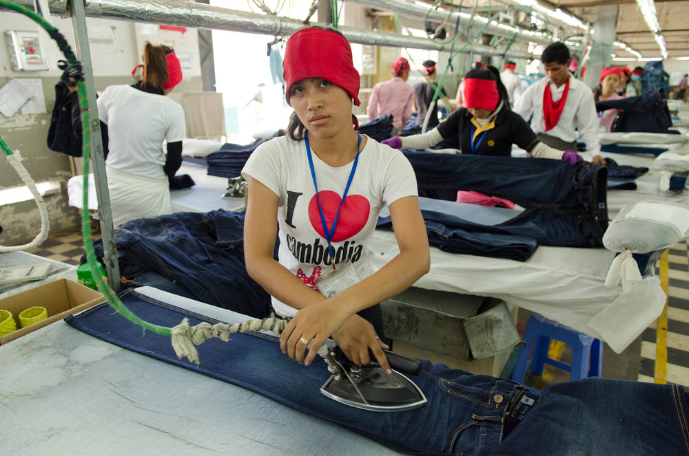 A young woman irons denim jeans with an industrial iron machine at the Meng Ieng Group garment factory in Phnom Penh. Cambodian garment factory work forces are made up almost entirely of young women and men are a rare minority.