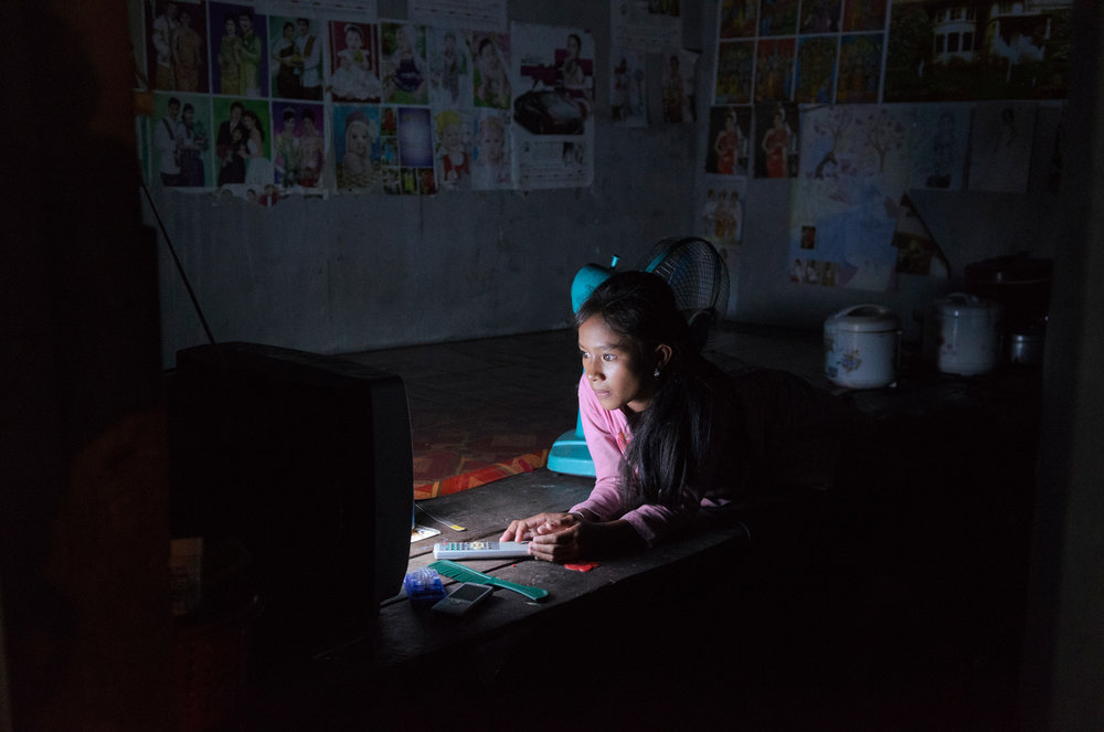 A young woman watches TV at night in the small one-room apartment she shares with others in one of the garment factory districts on the outskirts of Phnom Penh, Cambodia.