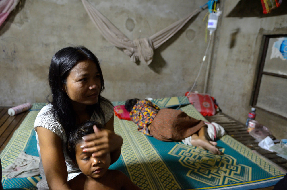 Mop Phak mops the brow of her son, Kan Khai, 7, in the small room she shares with several other people, including her sick mother, in the background. They live in an apartment complex that caters to garment factory workers.