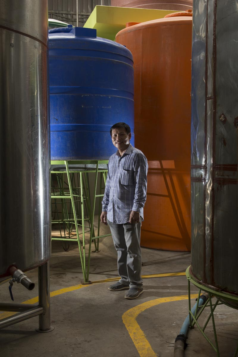 Owner Leang Leng stands amid the aging vats in his eponymous fish sauce factory in Phnom Penh.