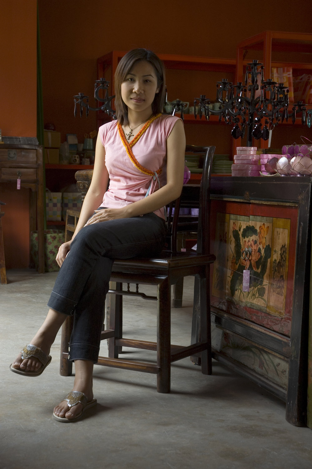 Salesperson Yui sits atop an antique Ningbo-style Chinese chair next to an antique Chinese chest at Ginger. The shop is well- known for its eclectic mix of modern and antique styles.