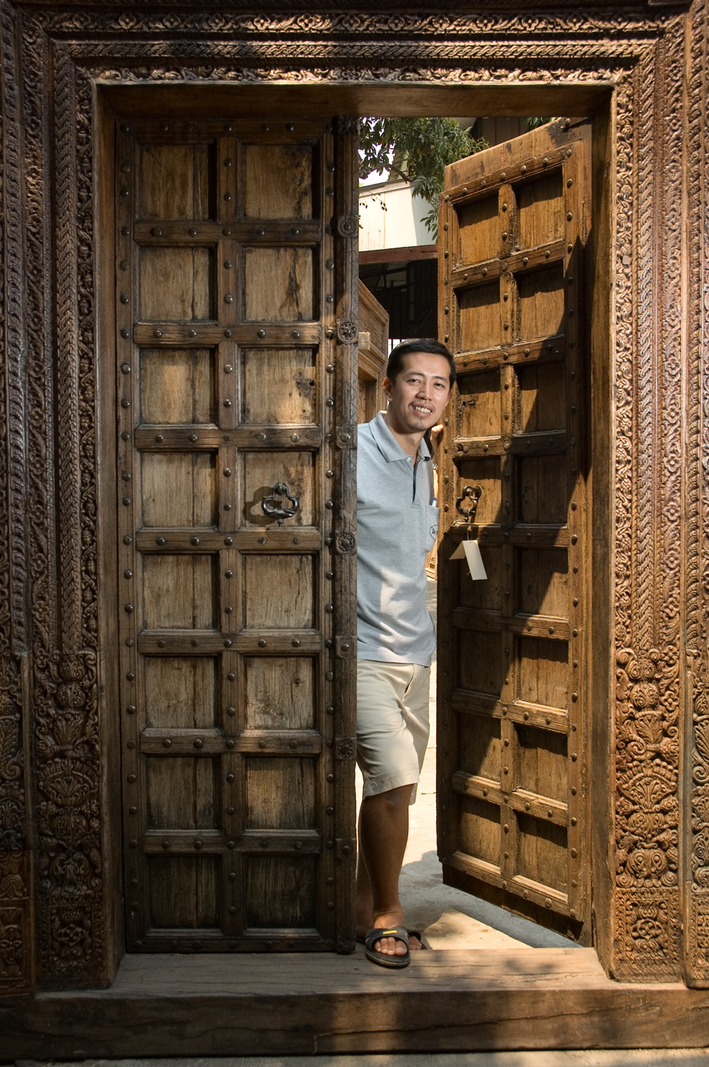 Anusak Parnichyakorn, owner of De Siam colonial and antique furniture store poses in one of the several antique Indian doorways he has on offer.