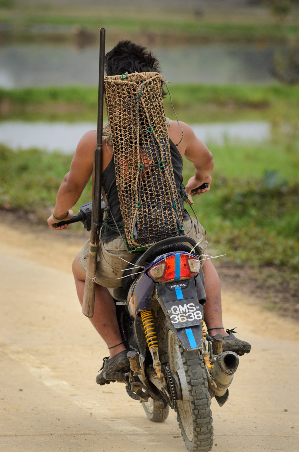 A young man on a motorcycle makes his way to the jungle with a hunting shotgun and a traditional Kelabit woven backpack to carry whatever he catches, in Bario, Sarawak, Malaysia.