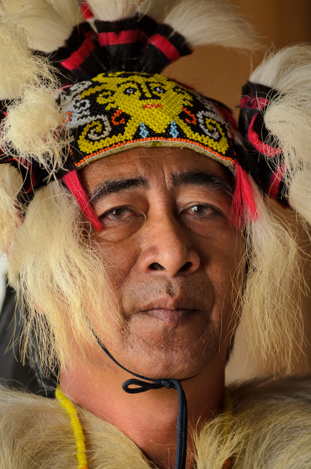 Portrait of Stephen Bala wearing his traditional Kelabit headdress in his home and guesthouse in Bario, Sarawak, Malaysia. Bala is a well-known regional artist who also works to preserve traditional Kelabit cultural traditions.