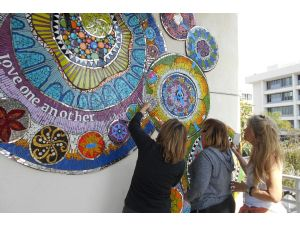 Katherine England, right, a local artist who teachers art programs in the Fullerton School Districts, oversees the placing of a mosaic mural at St. Jude Hospital. The mural was created by her students.