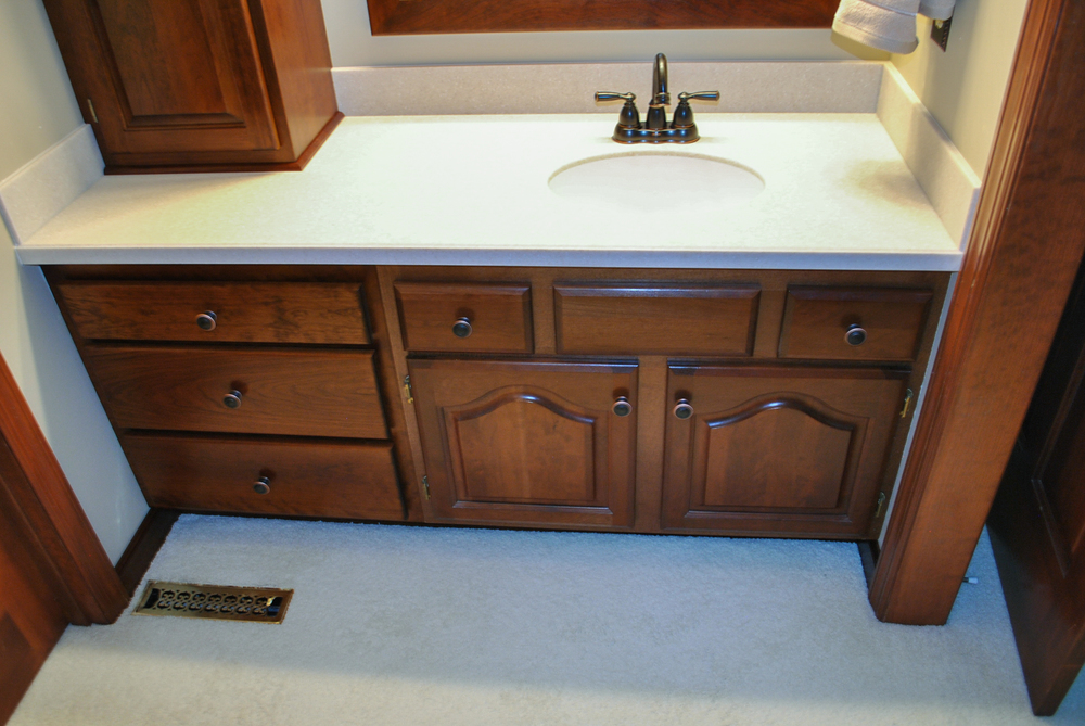 We replaced the existing single drawer at left with a three drawer cabinet. We also fabricated a new solid surface counter top with an under-mount sink.