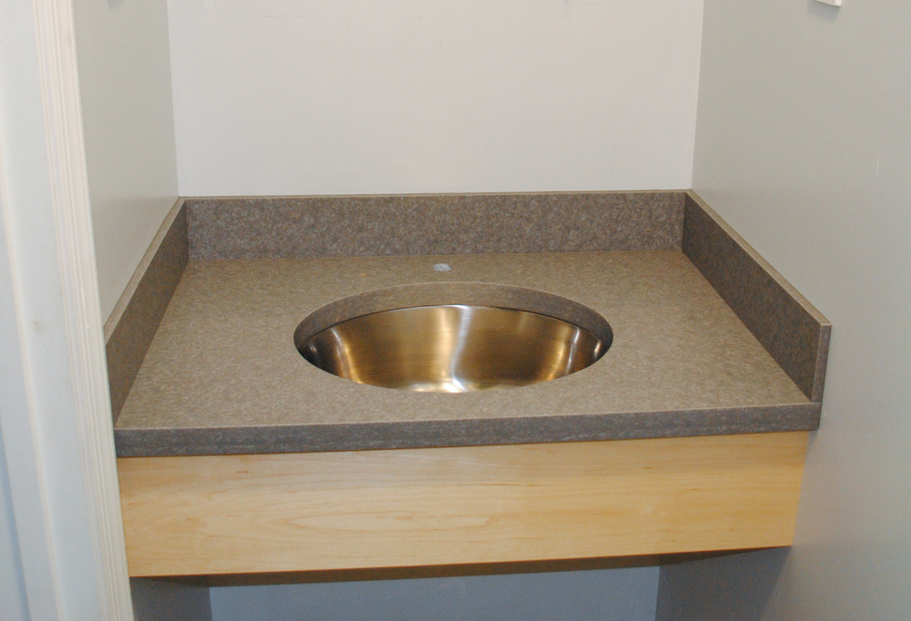 Solid surface top with under-mount stainless sink and maple veneer plywood apron. Note the double layer of build up at the sink and front counter edge. This gives a more robust look. Most tops are only built up at the front.