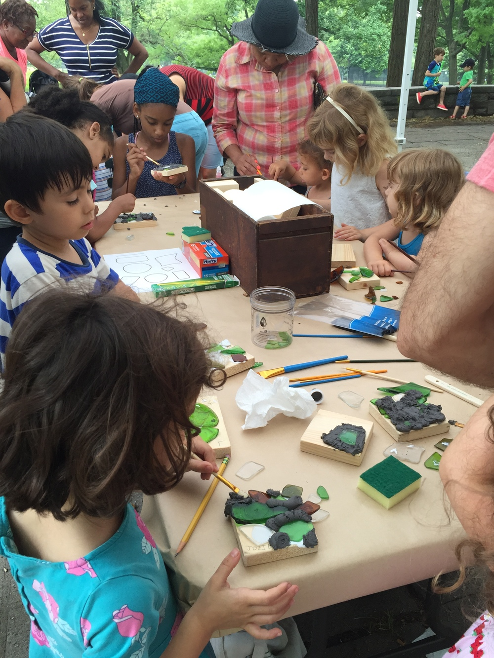 Children eagerly making their own unique mosaic tile with the historic glass pieces