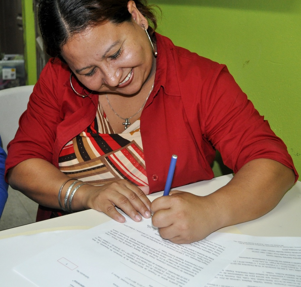 signing her first micro-loan papers 2013