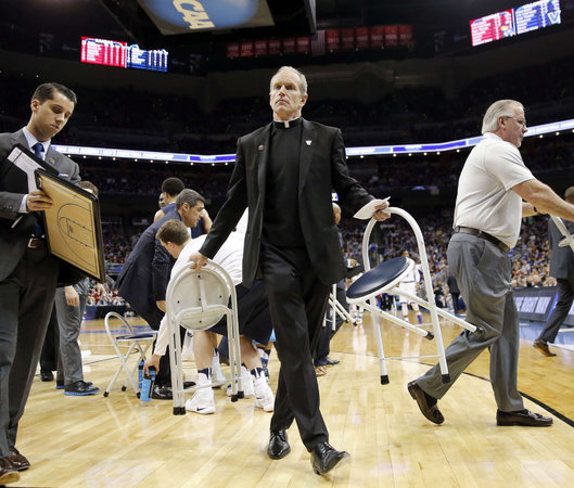 Father Rob Hagan helps with chairs during a timeout during Villanova's game against Kansas on Saturday night in Louisville, Ky. YONG KIM / Philly.com Staff Photographer