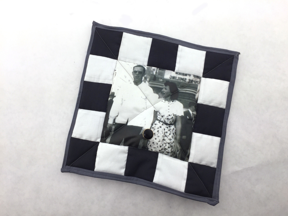 PROTOTYPE:  This miniature quilt has a speaker embedded in it's batting. When you press the decorative button, it plays the recording of a loved one, a story told by them about the photo in that patch.