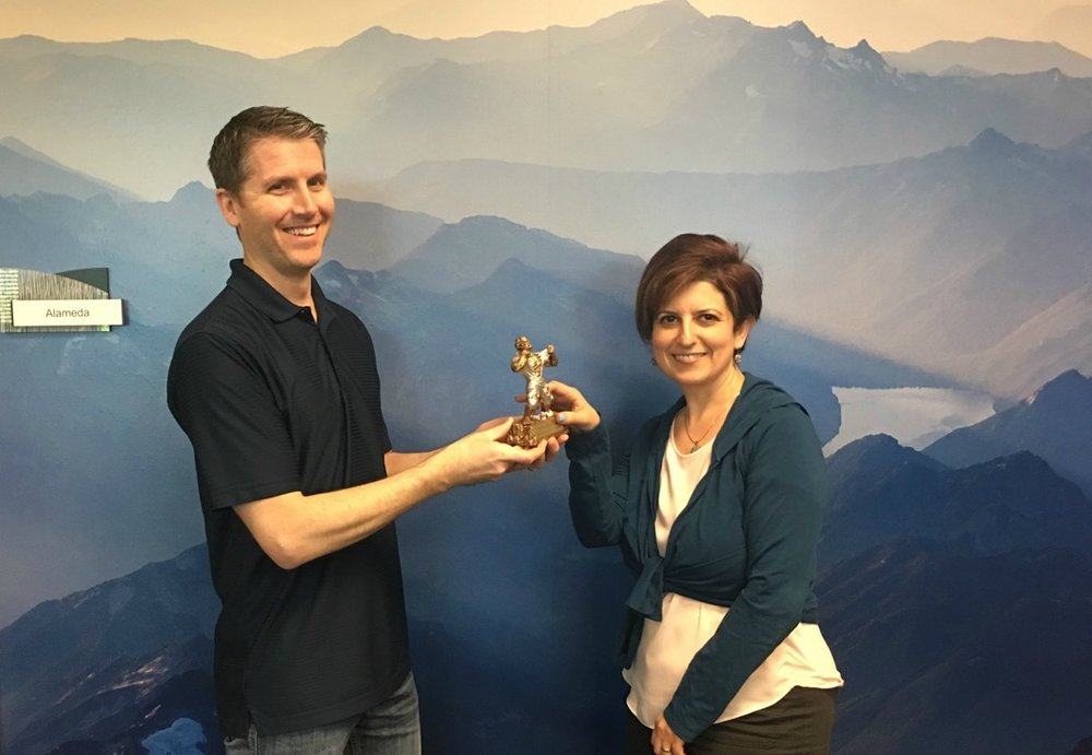 Patrick Kinsella, Software Developer and receipient of the Escape Employee of the First Quarter award, passing the batton to Arin Simonyan, HR/Payroll Software Support Lead and receipient of the Escape Employee of the Second Quarter award.