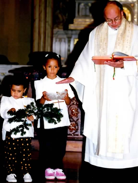 Two young Holy Trinity students assist Father Creason during mass