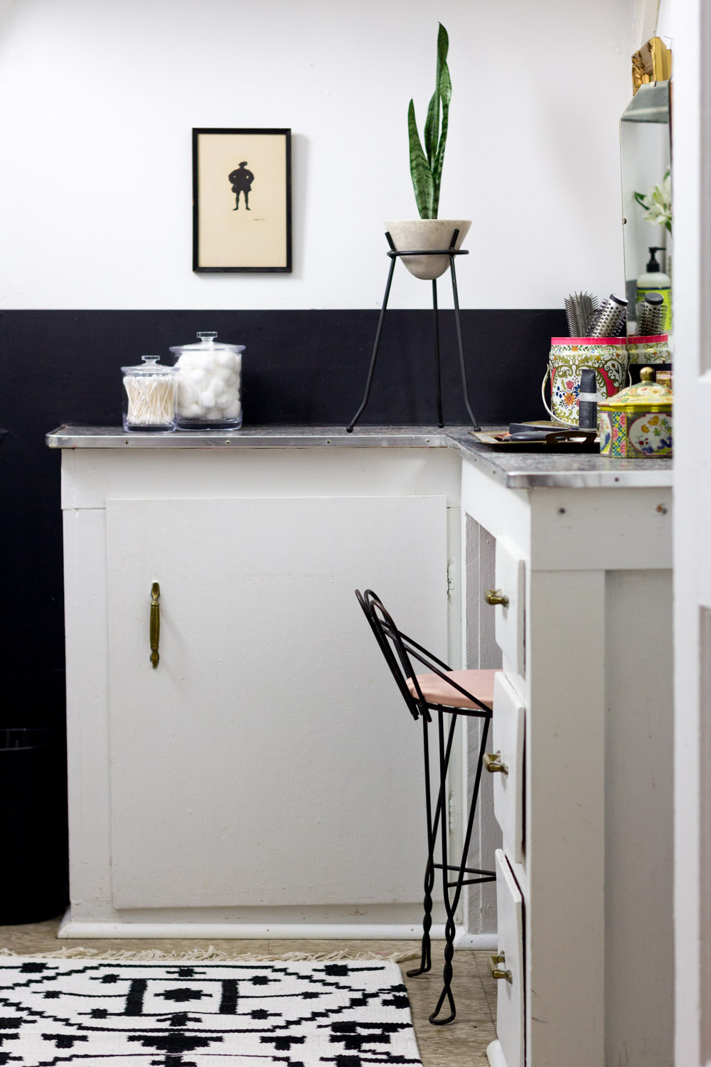 Black and white rental bathroom with pink vanity stool