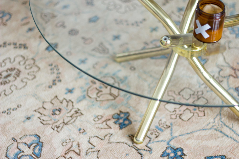 Brass and glass coffee table on neutral vintage area rug