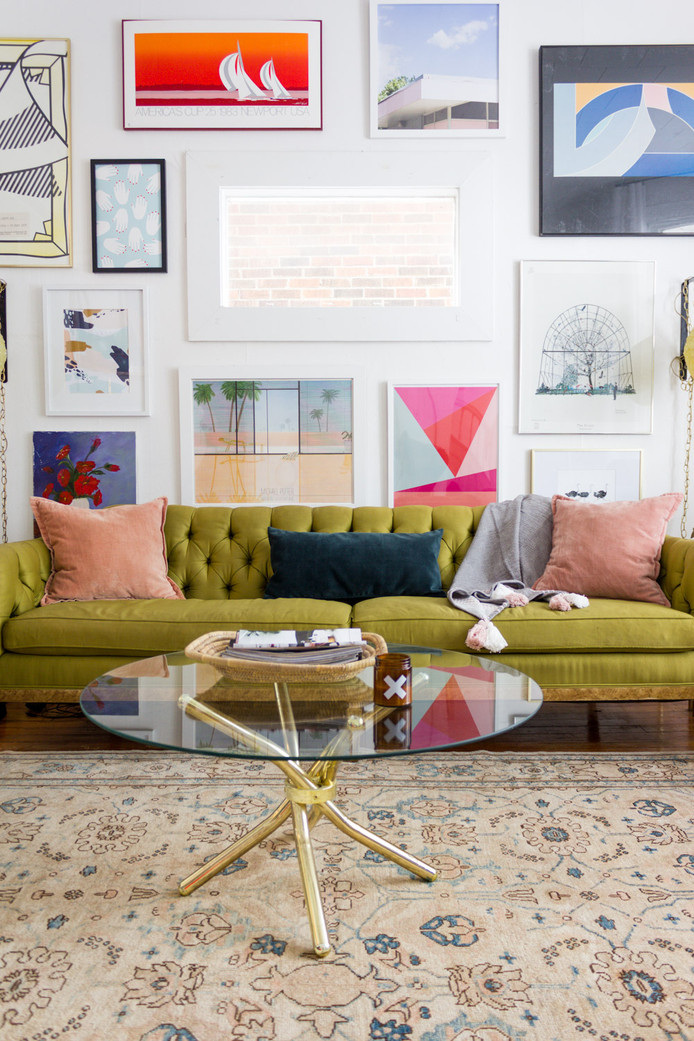 Colorful living room gallery wall with green tufted sofa and neutral vintage area rug