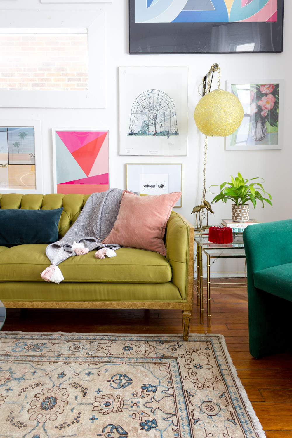 Colorful gallery wall with green tufted sofa and neutral vintage area rug