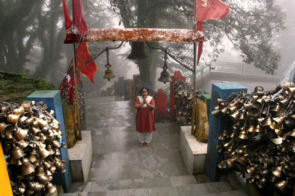 My friend Geeta lost in prayer, stands on the Drongiri temple steps. Image©gunjanvirk