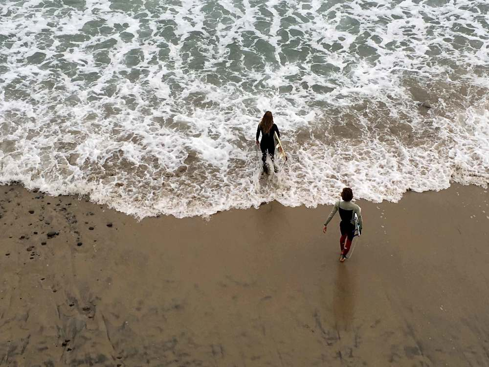 Surfers walking into the ocean, Swamis beach, Encinitas, California. Image©sourcingstyle.com
