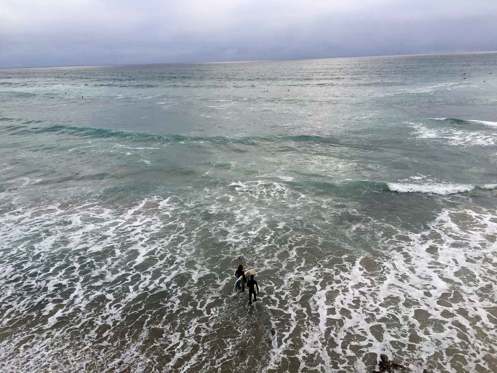 Surfers carrying surfboards, stormy day at the ocean, ocean view, Swamis beach, Encinitas, California. Image©sourcingstyle.com