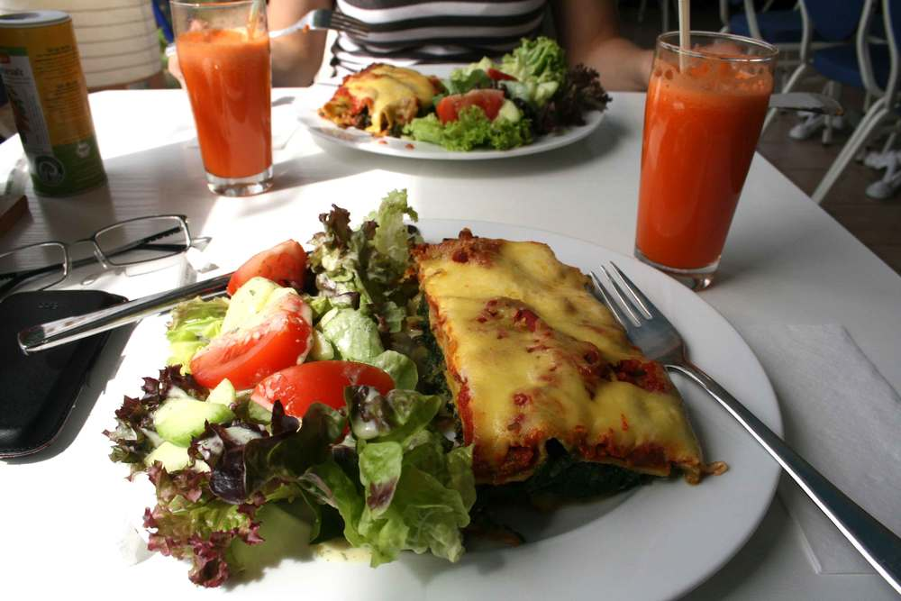 A plate of lasagna, salad and fresh carrot juice, vegan meal, vegetarian food, delicious, wholesome, healthy. Image©sourcingstyle.com