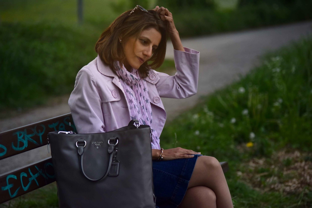Resting on a bench, village near Düsseldorf, Germany, pink trench, Ralph Lauren white tee, star scarf, Prada tote, Gucci sunglasses. Photo: Nicola Nolting, Image©sourcingstyle.com