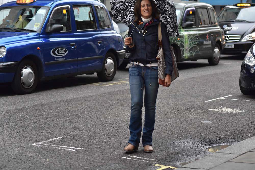 Zara water repellent jacket, Ralph Lauren polo sweater, Zara printed pocket square, Zara bandana print umbrella, True Religion jeans, Uggs boots, in front of London cabs, Covent Garden, London, UK. Image©sourcingstyle.com