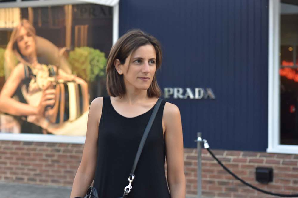 outside Prada store, Eileen Fisher jersey tank dress, Bicester village, designer shopping outlet near London, UK. Image©sourcingstyle.com