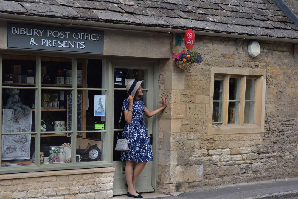 Prada dress, Prada ballet flats, Michael Kors bag, Bibury Post Office, Bibury, Cotswold, England. Image©sourcingstyle.com