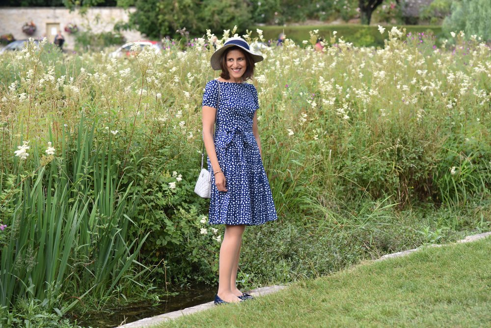 In a Prada dress, Prada ballet flats, Michael Kors bag, Arlington Fields, Bibury, Cotswold, England. Image©sourcingstyle.com