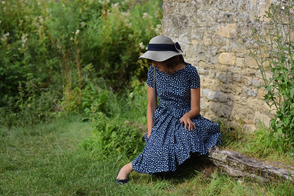 In a Prada dress, Prada ballet flats, Arlington Fields, Bibury, Cotswold, England. Image©sourcingstyle.com