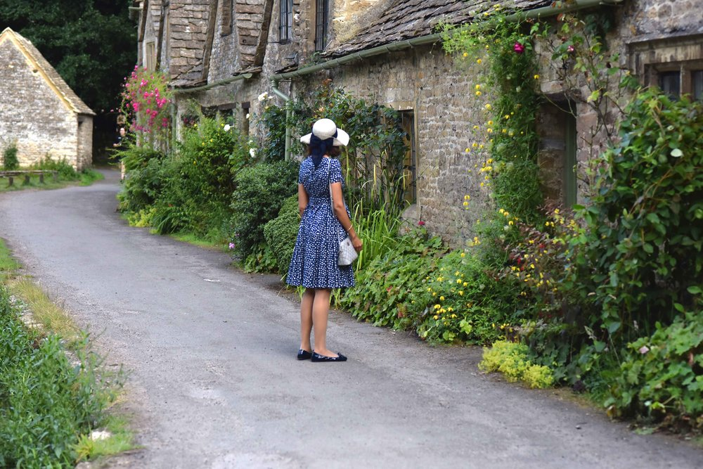 Prada dress, Prada ballet flats, Michael Kors bag, Cotswold stone cottages, Arlington Row, Bibury, Cotswold, England. Image©sourcingstyle.com