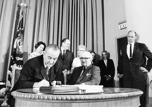 President Lyndon B. Johnson, left, with former President Harry S. Truman, signed the Medicare bill in 1965. ASSOCIATED PRESS