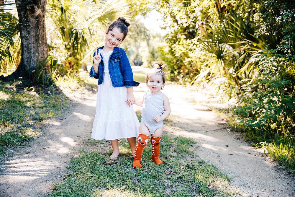 sisters-holding-hands-dirt-driveway.jpg